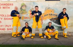 Group shot of Humber crew members lounging against a wall with lifeboat mural