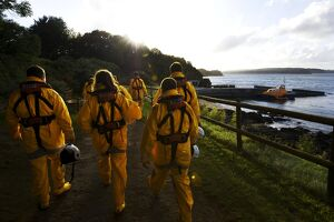 Group shot of the Tenby crew members walking along towards the Tamar class lifeboat