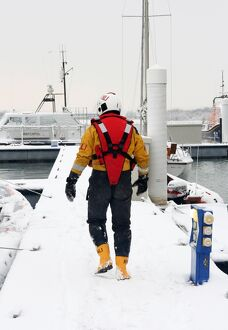 Lifeboat crew member walking along a snow covered pontoon