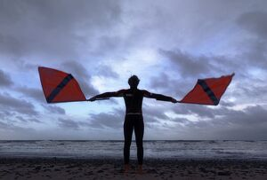 Lifeguard on Cromer beach waving two red flags. Silhouette.