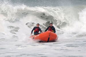 Two lifeguards on an arancia IRB in surf at St Agnes