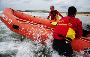 Two lifeguards launching an arancia inshore rescue boat at Constantine Bay, Cornwall