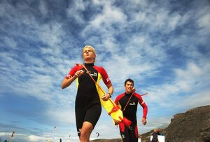 Two lifeguards running along the beach towards the camera, taken from below looking up