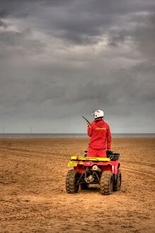 RNLI lifeguard on a quad bike patrol vehicle at Skegness beach.