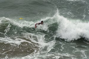 An RNLI lifeguard swimming through heavy surf at Perranporth