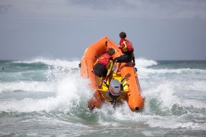 Two RNLI lifeguards heading through a breaking wave on an arancia inshore rescue boat