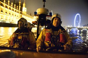 Tower lifeboat crew members on board an E-class lifeboat on the River Thames at night