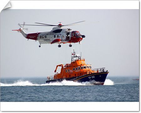 WeymouthSevern class lifeboat ON 1261 17-32 Ernest and Mabel. Close up of the boat travelling left to right with spray. A Coastguard helicopter is flying overhead. Summer 2003 Raw Courage & Professionalism