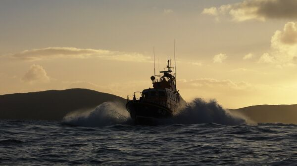 Achill Island trent class lifeboat Sam and Ada Moody 14-28. Lifeboat is heading towards the camera, silhouetted against a dramatic sky