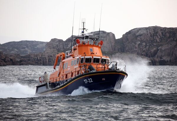 Arranmore severn class lifeboat Mrytle Maud 17-22 moving from left to right at speed, cliffs in the distance