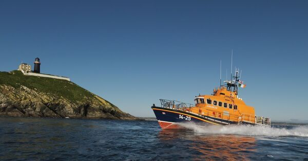 Ballycotton Trent Class lifeboat Austin Lidbury 14-25 moving from right to left, lighthouse in the background. Bright sunny day, blue sky