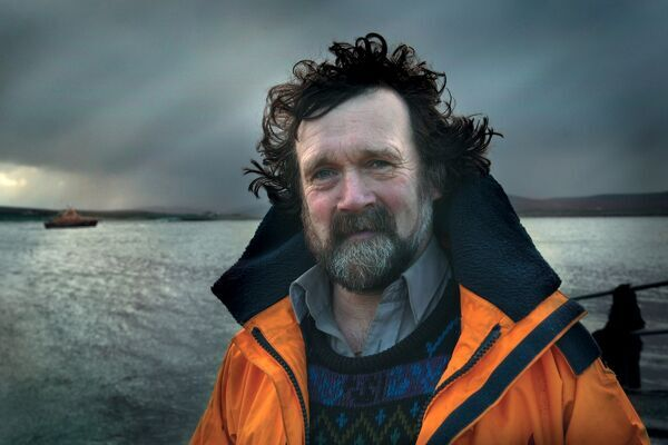 Ballyglass All Weather Lifeboat crewmember Michael Lally. Dark sky. Lifeboat in background out of focus