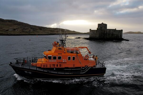 Barra Island severn class lifeboat Edna Windsor 17-12. ON 1230. Lifeboat is moving right to left in front of the castle in the harbour. Dramtic light shining through broken clouds