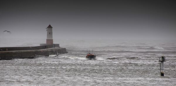 Berwick upon Tweed Mersey class lifeboat Joy and Charles Beeby 12-32 heading toward the camera in rough seas. Harbour wall and lighthouse to the left of the photo