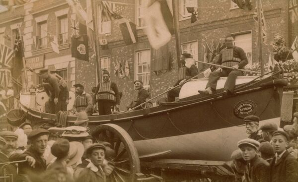 Chapel lifeboat Self Righter class ON 217 'John Alexander Berrey' on its carriage around the town. Lifeboat day. The town is decorated with flags, lots of people. Crew is wearing cork lifejackets. 1888 PART OF GRAHAME FARR ARCHIVES