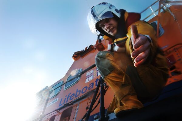 Crew member onboard Portrush Severn class lifeboat William Gordon Burr 17-30 reaching down towards the camera with hand extended