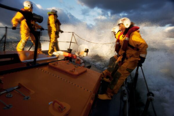 Crew members stood at the bow of the Berwick-upon-Tweed Mersey class lifeboat Joy and Charles Beeby 12-32, lots of spray