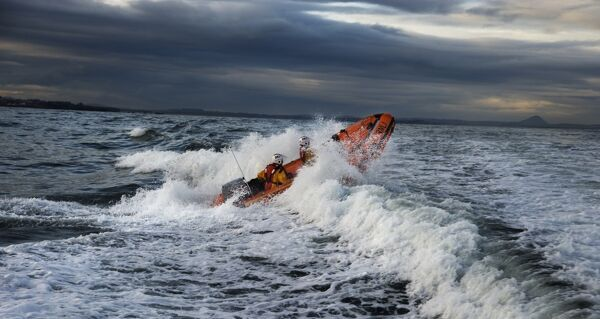 Dunbar D-class inshore lifeboat Jimmy Miff D-708. Two crew on board, lifeboat heading from left to right through a breaking wave