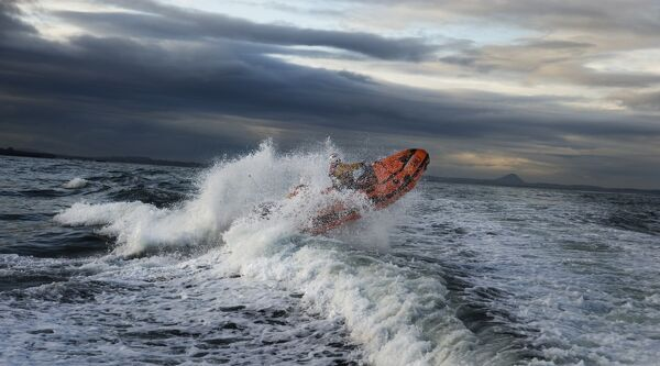 Dunbar D-class inshore lifeboat Jimmy Miff D-708.. Two crew on board, lifeboat heading from left to right through a breaking wave
