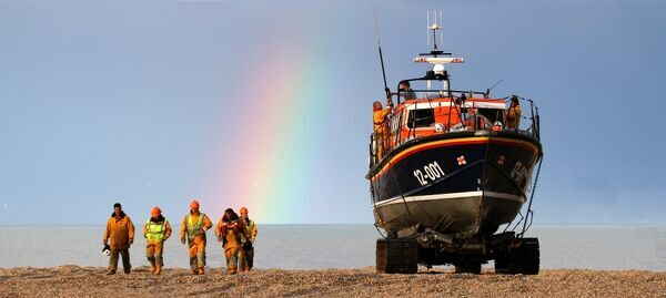 Dungeness relief mersey class lifeboat Peggy and Alex Caird returning from a service to a cabin cruiser. Crew walking along the beach, rainbow in the background. Shorlisted finallist for Photographer of the Year 2012