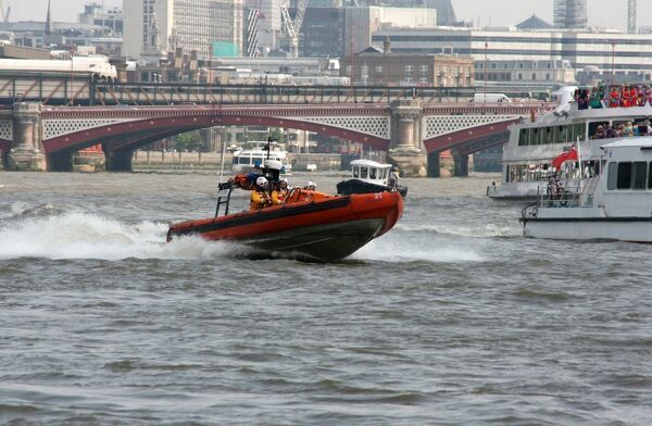 E-class lifeboat from Tower Lifeboat station on the Thames. Moving from left to right at speed, boats and city in the background