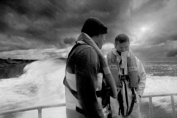Two falmouth crew members onboard the Severn class lifeboat Richard Cox Scott 17-29 during a training exercise. Shot in black and white, dark, moody and atmospheric image