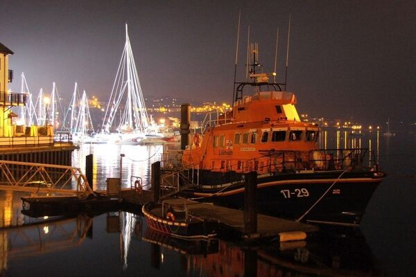 Falmouth severn class lifeboat Richard Cox Scott 17-29 ON 1256 at night. Lifeboat is moored outside the station, brightly lit yachts in the background