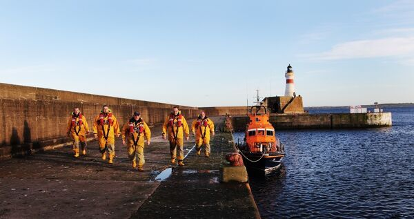 Fraserburgh crew members in full ALB kit next to the Trent class lifeboat Willie and Mary Gall 14-34 moored in the harbour