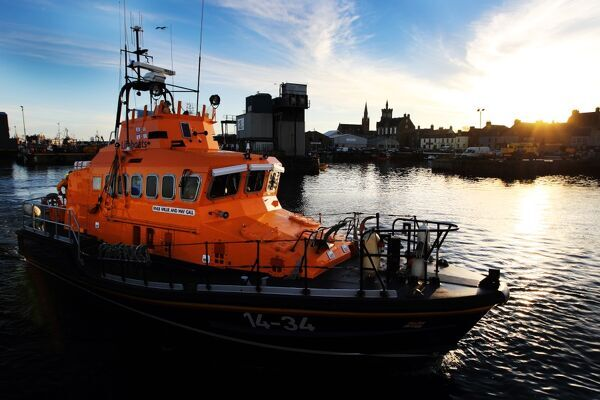 Fraserburgh Trent class lifeboat Willie and Mary Gall 14-34 in the harbour, sun low behind buildings in the background