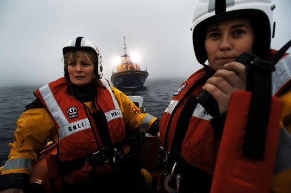 Kilmore Quay crew member Michelle Hinchy talking into a radio whilst on the Y-boat launched from the Tamar class lifeboat Killarney 16-18 which can be seen in the background with search lights on. Another female crew member at the helm