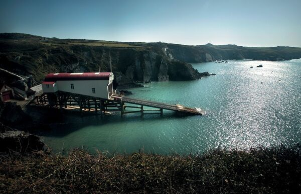 Lifeboat Station and slipway at St Davids, Wales. Calm sea, sunny day, cliffs of St Davids in background