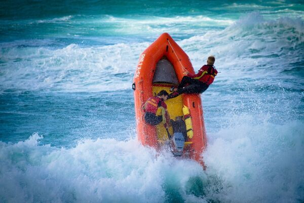 Lifeguards on an arancia inshore rescue boat in the surf at Perranporth beach, Cornwall