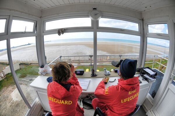 Two lifeguards monitoring the sea at a beach in Jersey from lifeguard hut