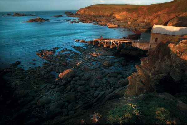 The Lizard Cornwall, to the right of picture, boathouse, slipway and cliffs.Left of picture sea Low light. Wide angle artistic shot. Aerial view