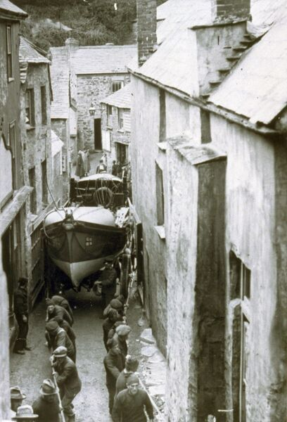 Self-righting lifeboat Richard and Sarah (built 1892) being pulled through the streets of Port Isaac, Cornwall ? known as ?passing the narrows?, c 1905