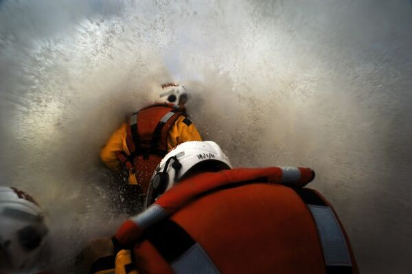 Three crew members on board Porthcawl Atlantic 85 inshore lifeboat Rose of the Shires B-832. Shot looking forward from the stern, rough seas and spray