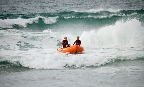 Two lifeguards on an arancia inshore rescue boat in the surf at Porthtowan