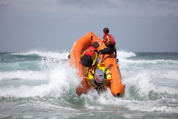 Two RNLI lifeguards heading through a breaking wave on an arancia inshore rescue boat, bow high out of the water