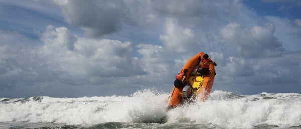 Two RNLI lifeguards heading over a breaking wave at Woolacombe beach, Devon on an arancia inshore rescue boat, bow high out of the water