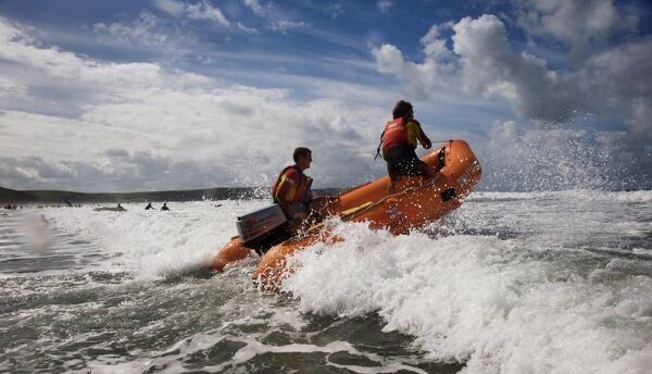 Two RNLI lifeguards in the surf at Woolacombe beach, Devon on an arancia inshore rescue boat