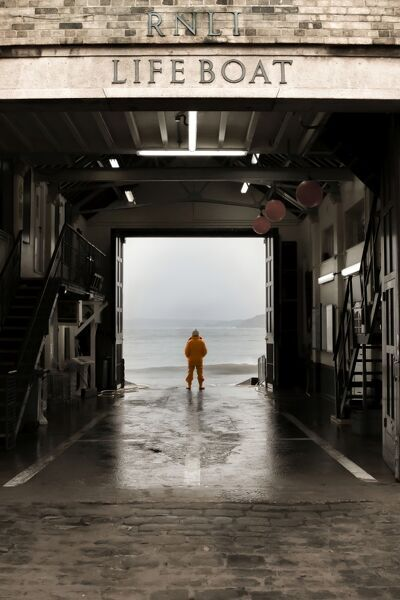 This is an image of a member of the Scarborough RNLI team who is looking out from the boathouse to the sea where the rest of his crew were training
