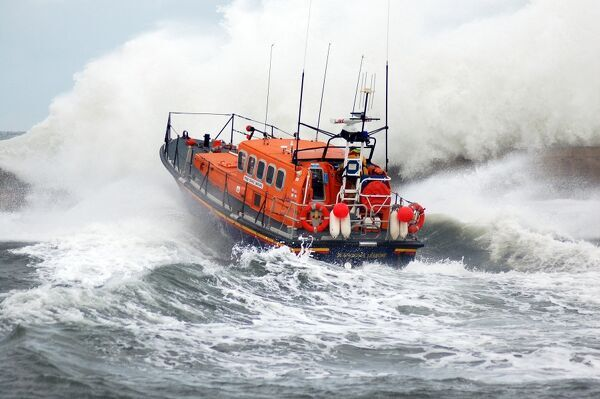 Seahouses mersey class lifeboat Grace Darling 12-16. Lifeboat heading away from the camera, crew at the upper steering position, huge waves breaking over the sea wall