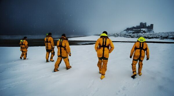Five Seahouses RNLI crew members walking along a snow covered beach, Bamburgh Castle in the distance