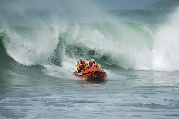 St Agnes Lifeboat Day. D-class lifeboat Blue Peter IV D-641 with crew onboard, large wave following the lifeboat