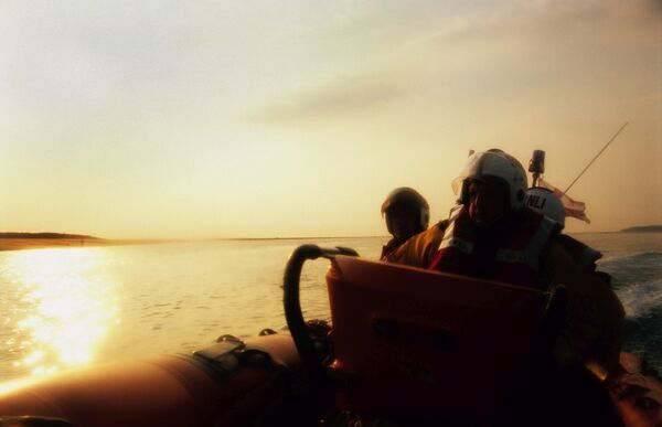 Sunset from the lifeboat. 3 crew members visible. Calm seas. Boat to the right side of the picture