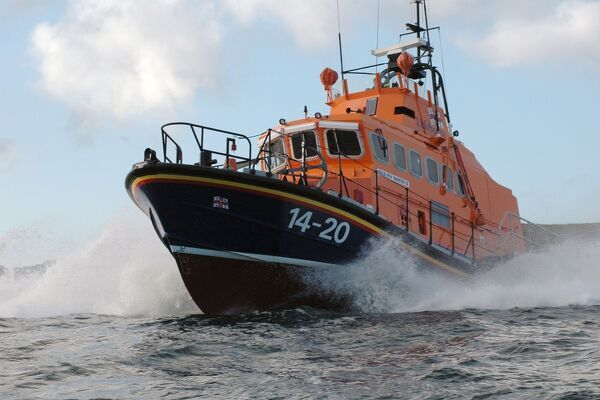 Wick Trent class lifeboat Roy Barker II 14-20, ON 1210. Lifeboat is moving from right to left towards the camera, blue sky and sea, white spray