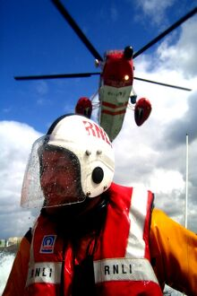 Portrait shot of a coastguard helicopter above an RNLI ILB crew
