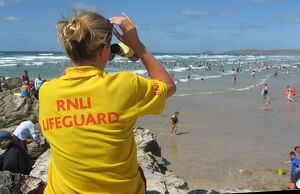 An RNLI lifeguard monitoring the busy Perranporth beach