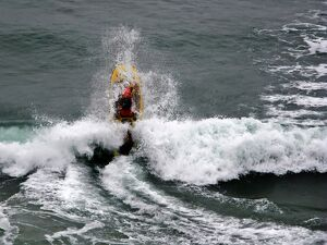 An RNLI lifeguard on a rescue water craft at Perranporth