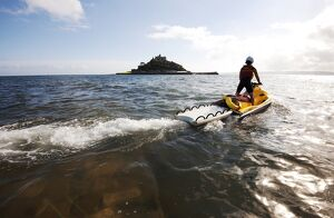 RNLI lifeguard on a rescue watercraft (RWC) with St Michael's Mount near Penzance
